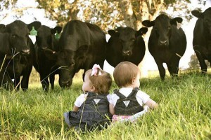 two babies in front of a herd of cows