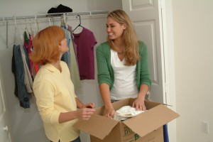two women smiling and packing clothes