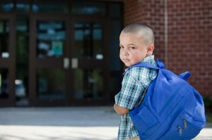 little boy wearing a blue backpack about to walk into school