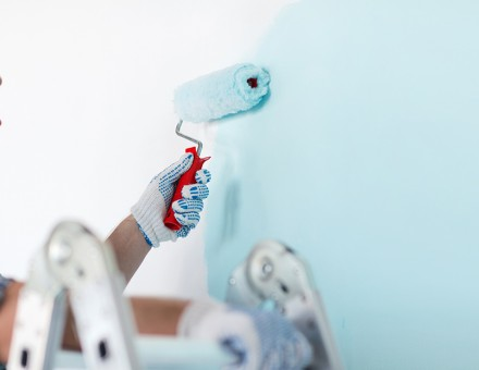 man painting a wall light blue