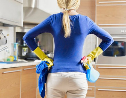 woman in the kitchen holding cleaning supplies