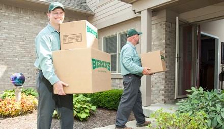 bekins workers bringing boxes inside new home