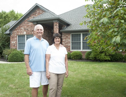 older couple in front of brick house