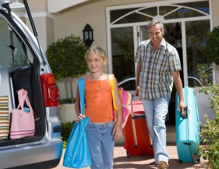Girl (6-8) and father loading car with luggage, smiling, low angle view