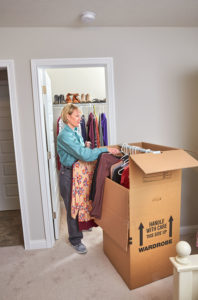 woman packing a wardrobe box