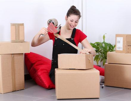 girl taping a moving box