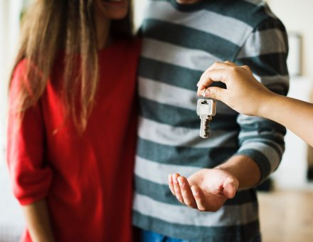 person handing keys to a couple
