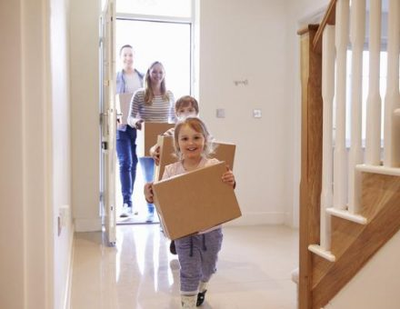 A family moving into their new home, every person with a box to carry