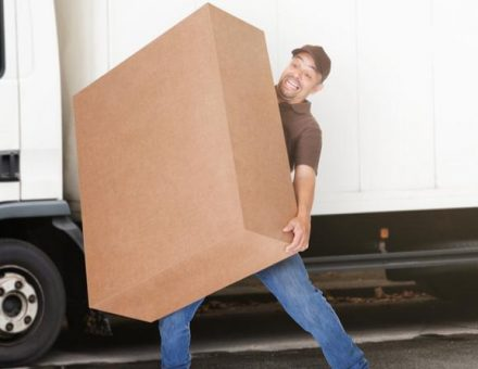 Mover struggling with oversized box in front of moving truck