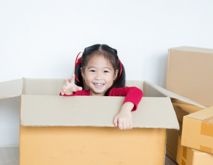 Smiling little girl playing inside an open cardboard box. How to get your kids invested in your move