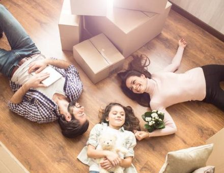 Family happily laying on the floor of their new home shortly after moving in from out-of-state