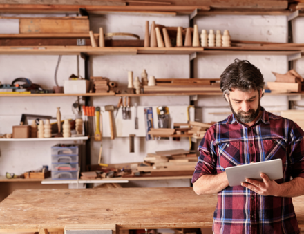 Small business owner consulting a list on his clipboard. How to move shop when you're a small business owner