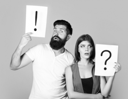 An exasperated couple holding up exclamation point and question mark signs