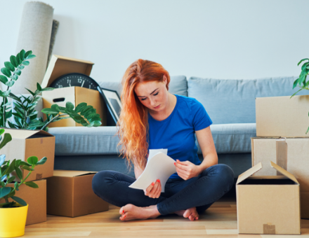 Women sitting by moving boxes reading paper