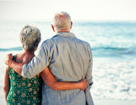 Older couple embracing in front of ocean