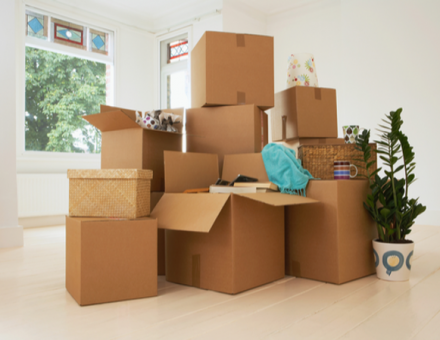 Cardboard boxes stacked in empty room