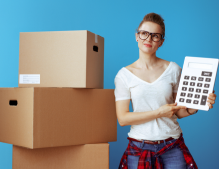 women with large calculator standing next to moving boxes