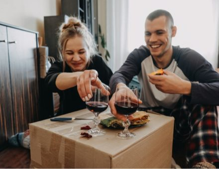 Couple unpacking and eating on a cardboard box after moving