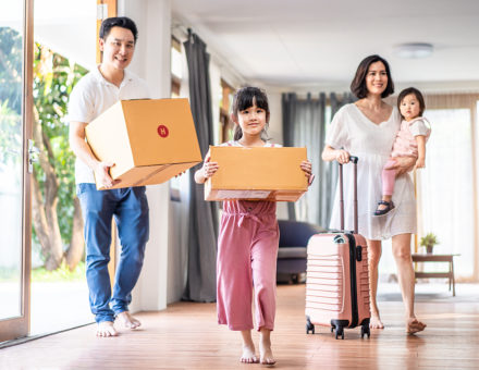 Large family carrying boxes into their new home