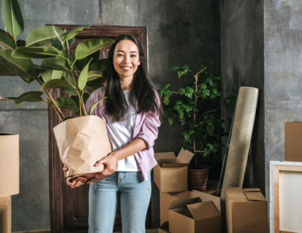 young woman with ficus plant and boxes moving into new house