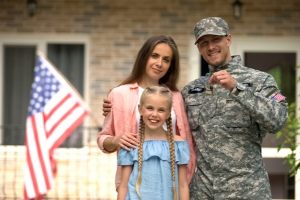 A military spouse and family stand in front of their new home