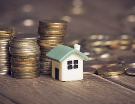 mortgage payment: coins sitting by house